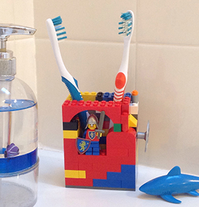 Photo of bathroom sink counter with soap dispenser, plastic shark toy, and toothbrush holder made from Legos.