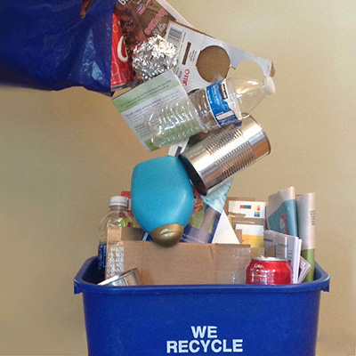 Recyclable materials falling loose into a curbside bin